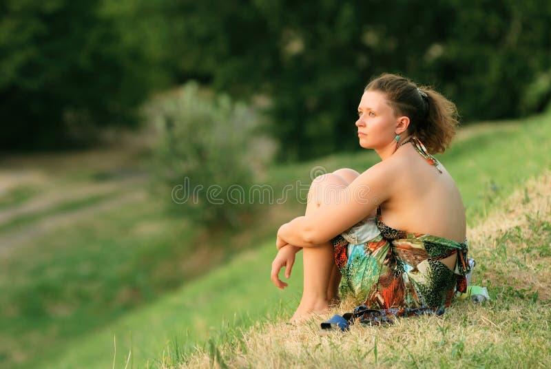 Jeune femme s'asseyant sur l'herbe images libres de droits