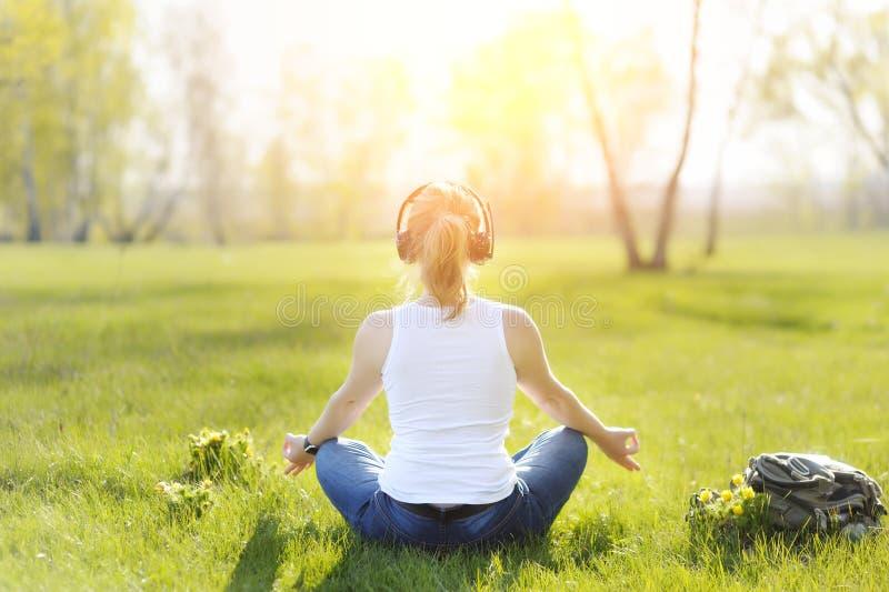 Jeune femme s'asseyant sur l'herbe en parc et méditer et listenin photographie stock
