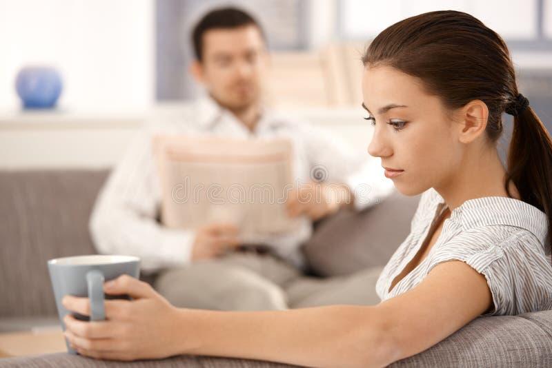 Jeune femme s'asseyant sur l'homme de sofa à l'arrière-plan images libres de droits