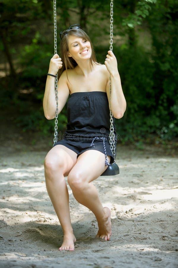 Jeune femme s'asseyant sur l'oscillation au terrain de jeu image libre de droits