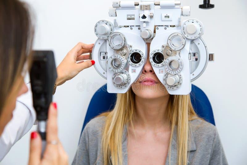 Jeune femme s'asseyant sur la chaise avec la belle position d'opticien tout en faisant l'essai d'oeil dans la clinique d'ophthalm photos libres de droits