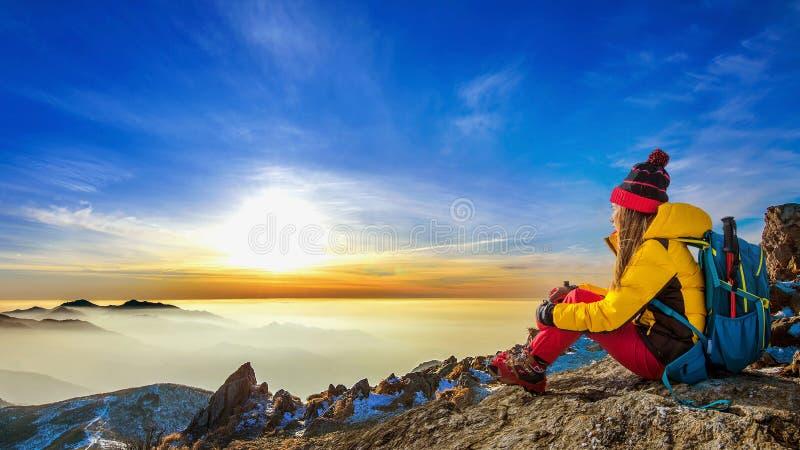 Jeune femme s'asseyant sur la colline de hautes montagnes photo stock