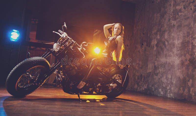 Jeune femme s'asseyant sur la moto image stock