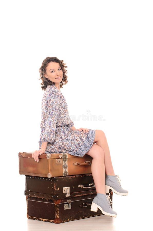 jeune femme s'asseyant sur la pile de valises images libres de droits