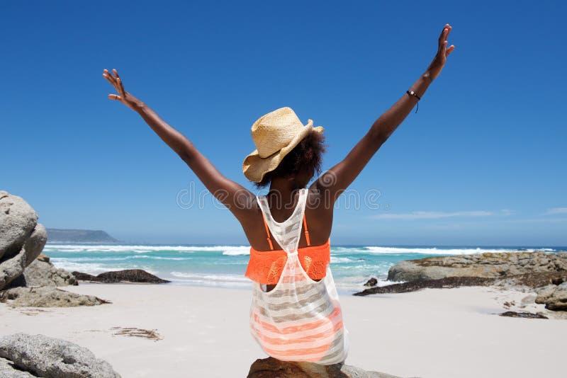 Jeune femme s'asseyant sur la plage avec ses mains tendues photos libres de droits