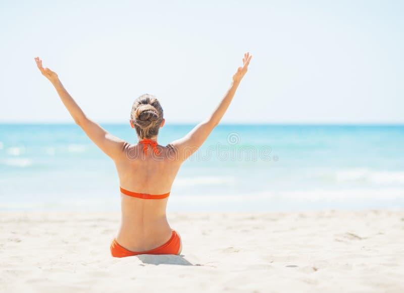 Jeune femme s'asseyant sur la plage et se réjouissant image libre de droits