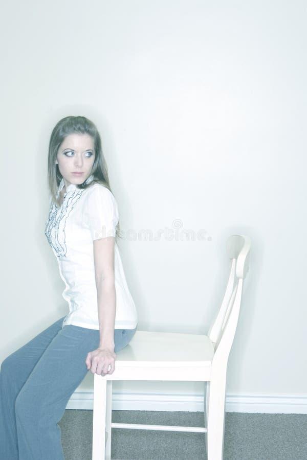 Jeune femme s'asseyant sur la présidence images stock