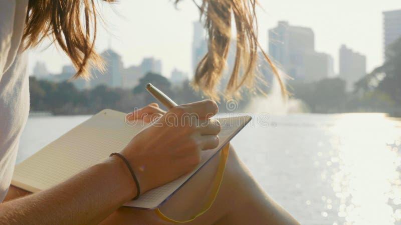 Jeune femme s'asseyant sur le banc en parc et écrivant en journal intime, plan rapproché photo libre de droits