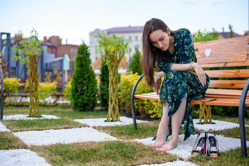 Jeune femme s'asseyant sur le banc nu-pieds à côté des chaussures de talon haut, repos des chaussures photos libres de droits