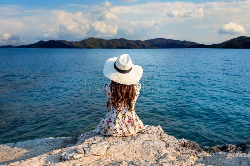 Jeune femme s'asseyant sur le dessus de la roche et regardant le bord de la mer photos libres de droits