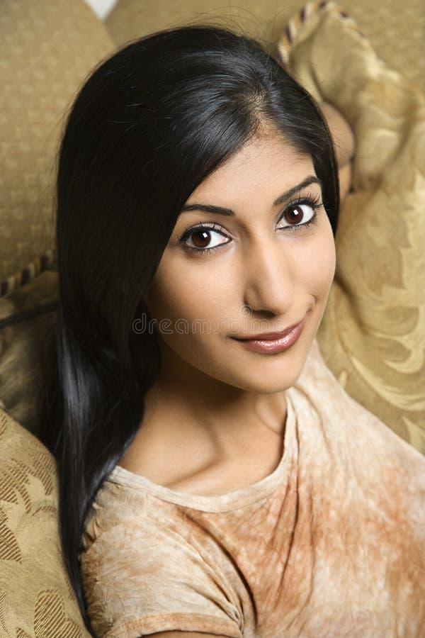 Jeune femme s'asseyant sur le divan. image stock