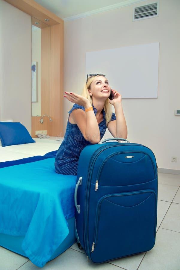 Jeune femme s'asseyant sur le lit dans la chambre d'hôtel et parlant à un téléphone portable photos libres de droits