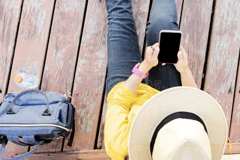 Jeune femme s'asseyant sur le plancher en bois avec le téléphone portable image libre de droits