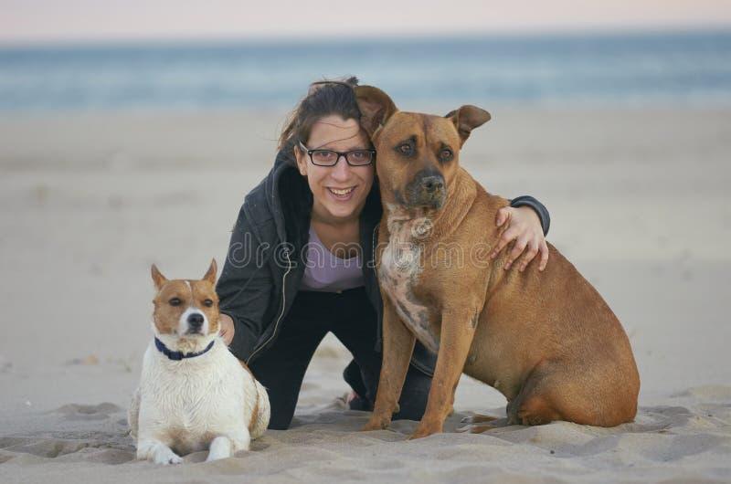 Jeune femme s'asseyant sur le sable avec ses chiens sur une plage images stock