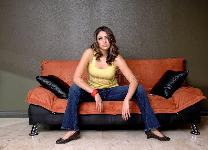 Jeune femme s'asseyant sur le sofa photo libre de droits