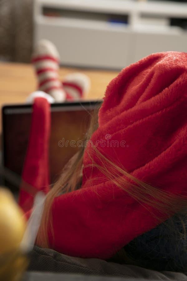 Jeune femme s'asseyant sur le sofa, utilisations un ordinateur portable, vue de dos images libres de droits