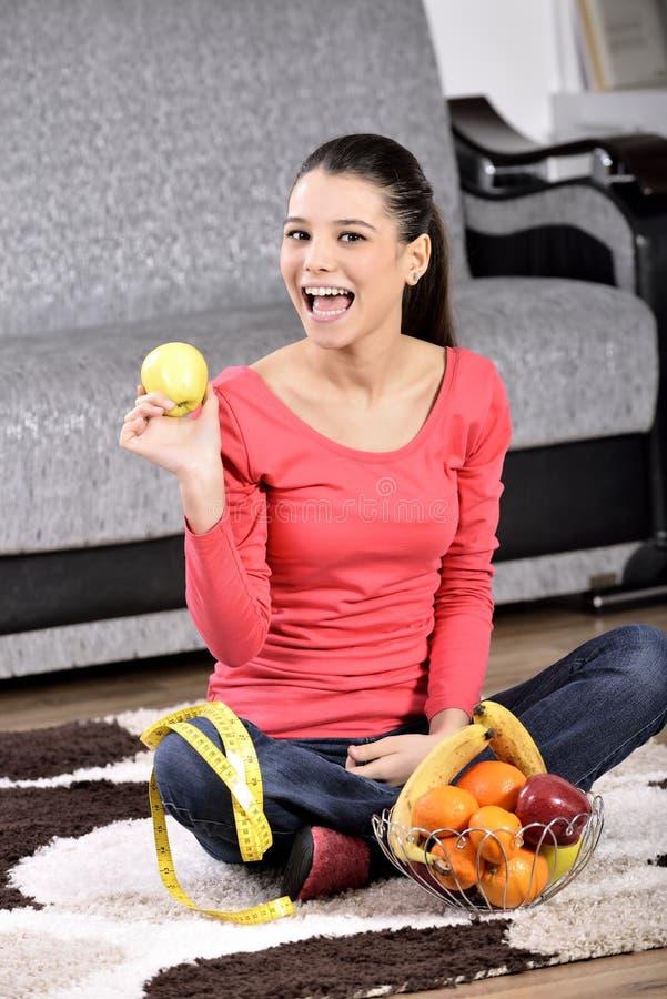 Jeune femme s'asseyant sur le tapis et appréciant des fruits photographie stock libre de droits