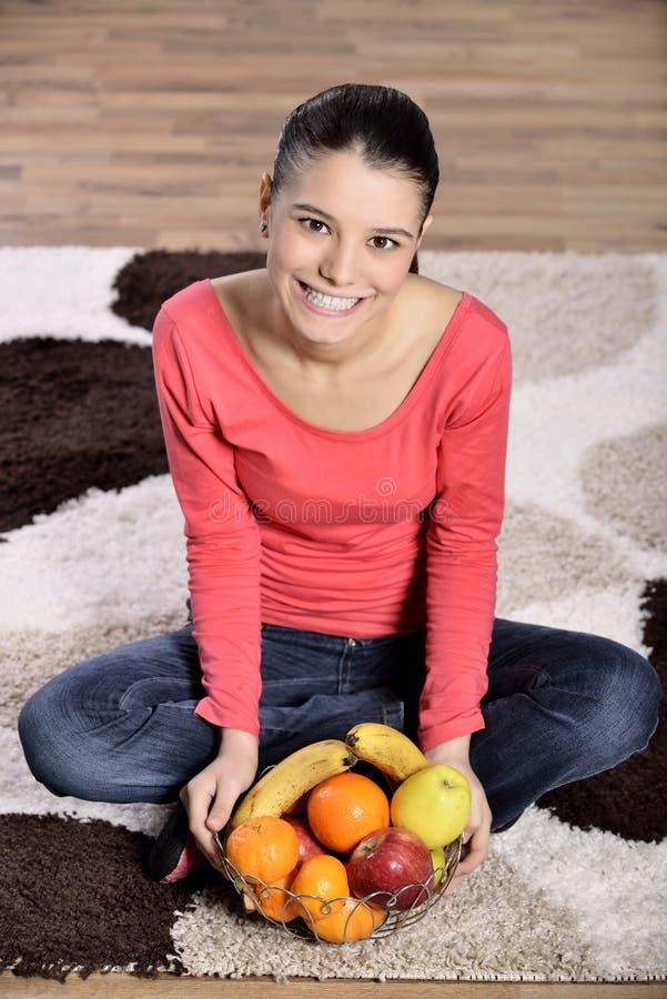 Jeune femme s'asseyant sur le tapis et appréciant des fruits image libre de droits