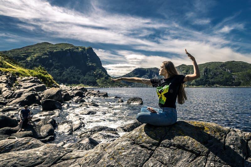 Jeune femme s'asseyant sur les roches, Norvège images stock