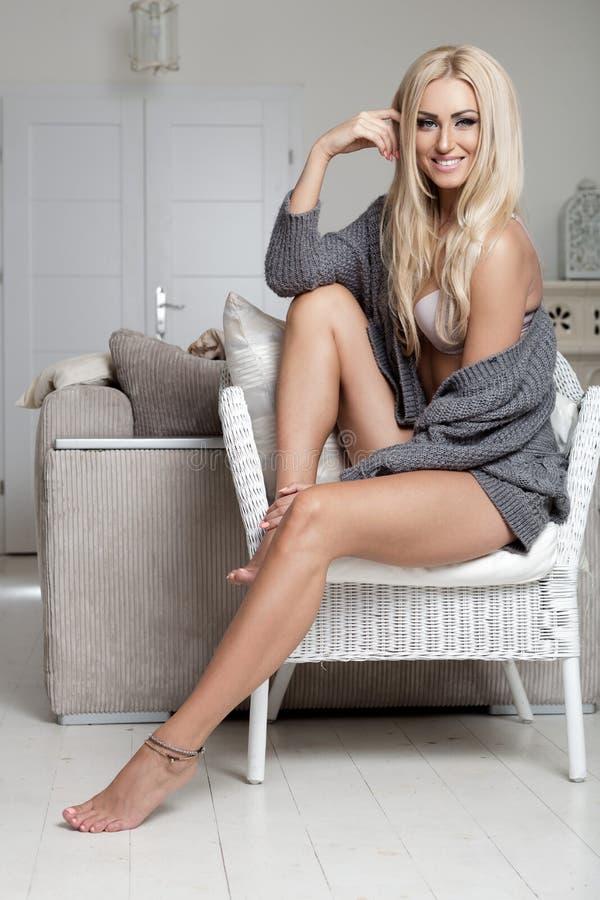 Jeune femme s'asseyant sur un fauteuil Humeur confortable photos libres de droits