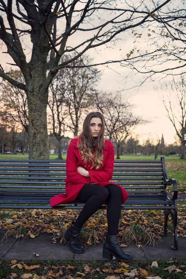 Jeune femme s'asseyant sur un sentiment de banc de parc malheureux images stock