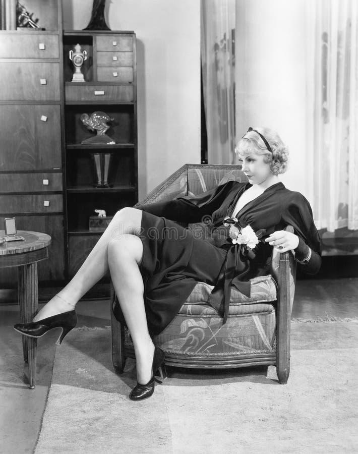 Jeune femme s'asseyant sur une chaise dans son salon, contemplant (toutes les personnes représentées ne sont pas plus long vivant images stock
