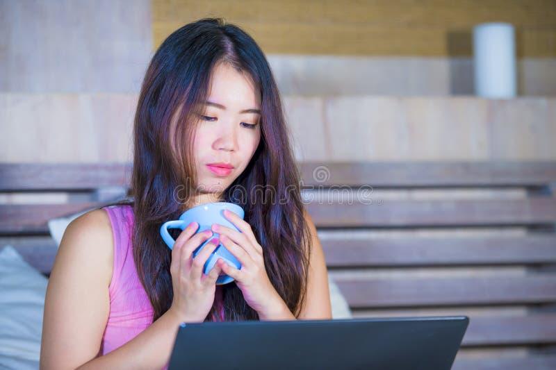 Jeune femme 20s chinoise asiatique attirante et belle se trouvant sur le lit la nuit utilisant l'Internet dans le film d'ordinate images stock