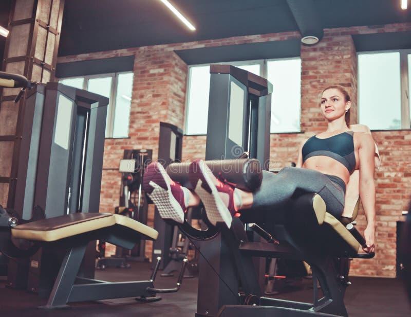 jeune femme s'exerçant avec la machine d'extension de jambe images libres de droits