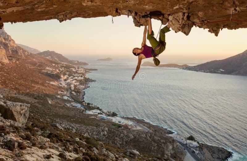 Jeune femme s'?levant en caverne au coucher du soleil images libres de droits