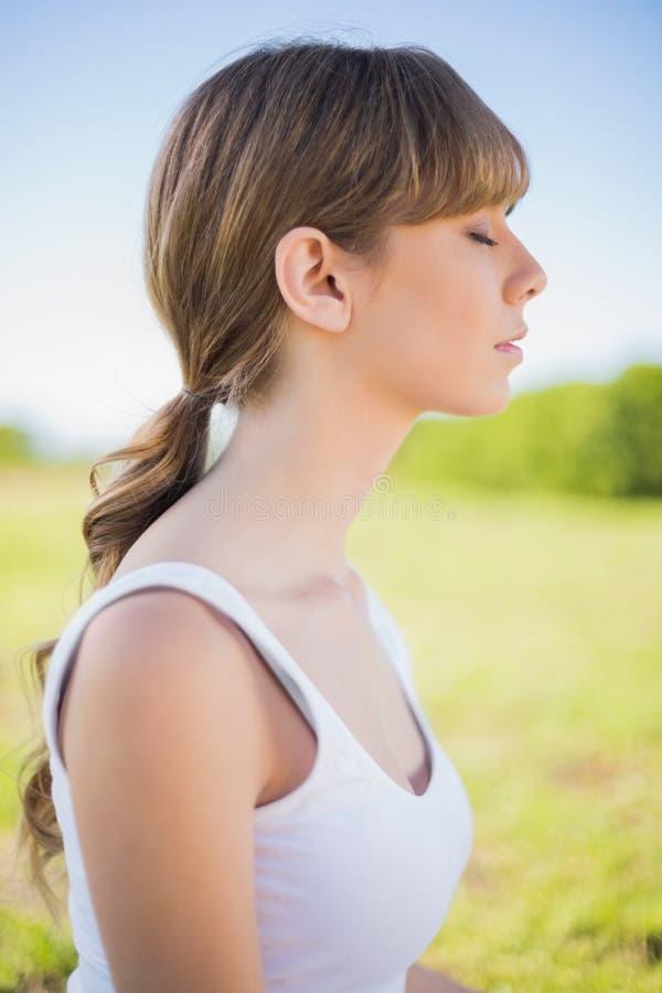 Jeune femme satisfaite posant dehors images stock
