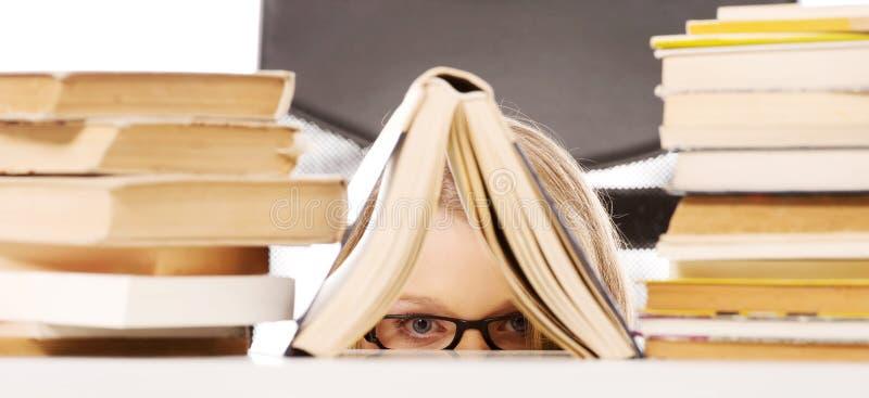Jeune femme se cachant derrière un livre photo libre de droits