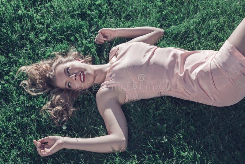 Jeune femme se couchant sur l'herbe photos stock