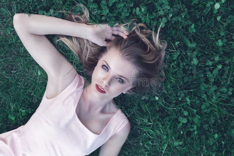 Jeune femme se couchant sur l'herbe photo libre de droits
