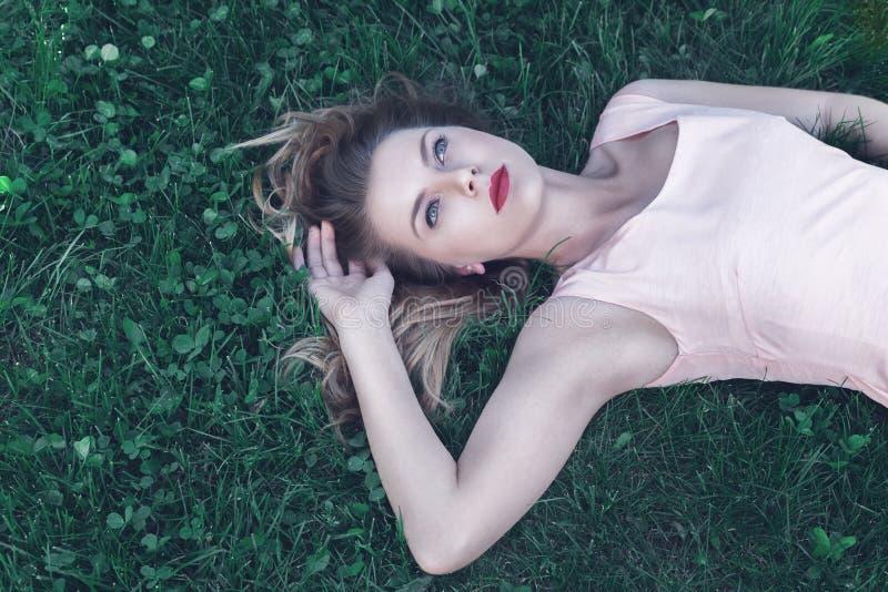 Jeune femme se couchant sur l'herbe image libre de droits