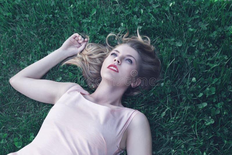 Jeune femme se couchant sur l'herbe photographie stock