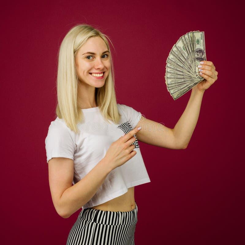 Jeune femme se dirigeant vers une pile d'argent avec son doigt d'isolement sur le fond rouge photos libres de droits