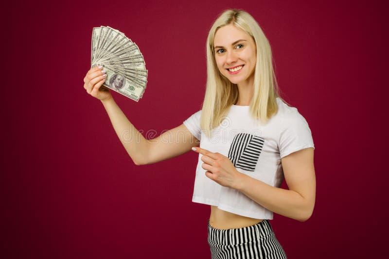 Jeune femme se dirigeant vers une pile d'argent avec son doigt d'isolement sur le fond rouge image libre de droits