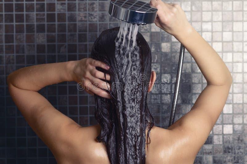 Jeune femme se lavant les longs cheveux sous la douche photographie stock