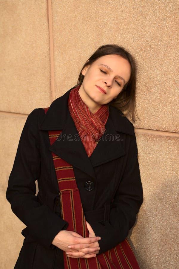 Jeune femme se penchant contre le fléau images stock