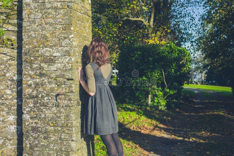 Jeune femme se penchant contre le mur en pierre photo libre de droits
