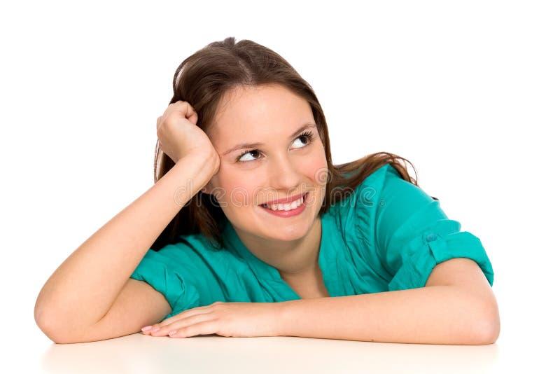 Jeune femme se penchant sur la table images stock