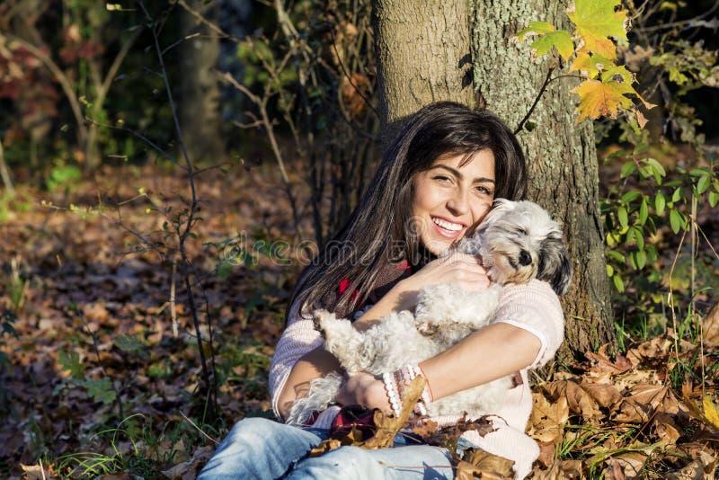 Jeune femme se penchant sur un arbre d'automne étreignant son chien photo libre de droits