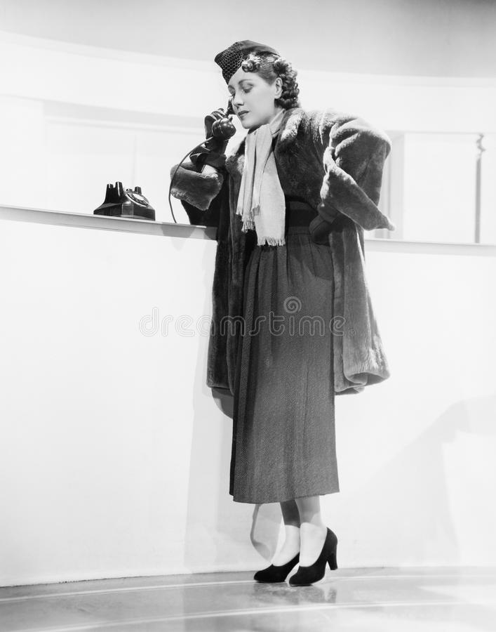 Jeune femme se penchant sur un compteur et parlant au téléphone (toutes les personnes représentées ne sont pas plus long vivantes photos stock