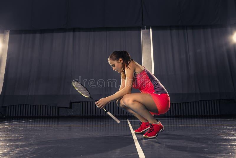 Jeune femme se reposant après avoir joué le badminton au gymnase photos libres de droits