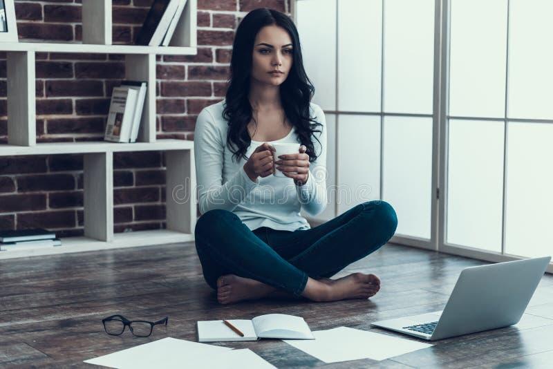 Jeune femme se reposant après travail avec la tasse de café photos stock