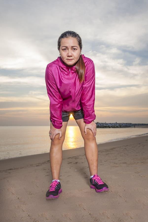 Jeune femme se reposant après un fonctionnement actif tout en se tenant contre sur la plage photographie stock