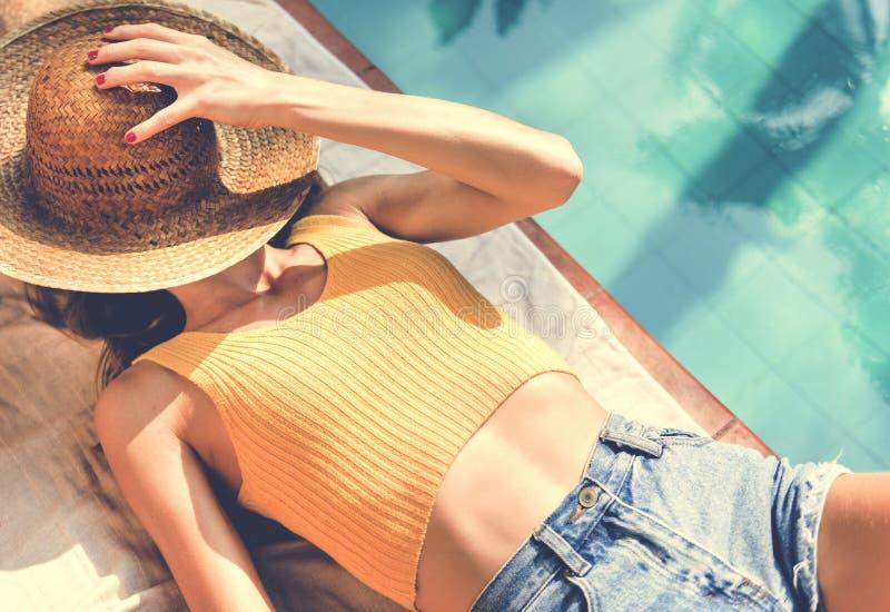 Jeune femme se reposant sur le poolside photographie stock