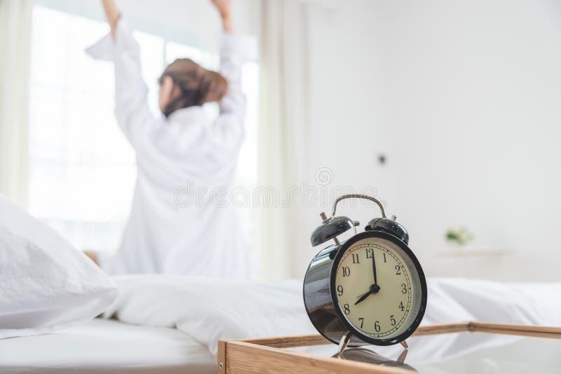 Jeune femme se situant dans le lit dans le matin image stock