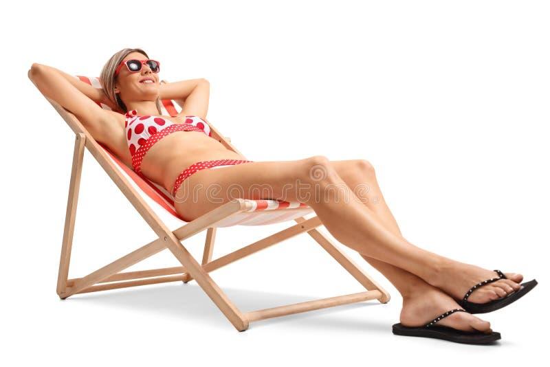 Jeune femme se situant dans une chaise de plate-forme image stock