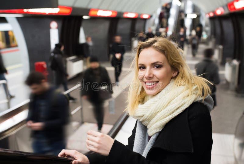 Jeune femme se tenant à l'escalator dans le souterrain de Vienne image libre de droits
